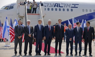 Men in suits stand in one line before airplane
