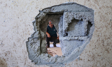 Man looks through hole in wall