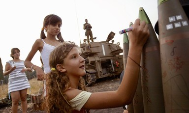 Smiling girl writes on munition as others look on