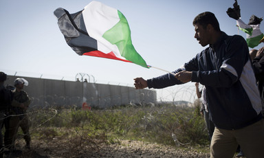 Man holding Palestine flag grabs barbed wire fence near Israeli soldiers