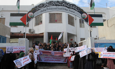 A group of people - some carrying flags and banners - stand outside a building