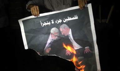 Man holds burning poster of two men