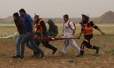 Medics rush an injured demonstrator to safety