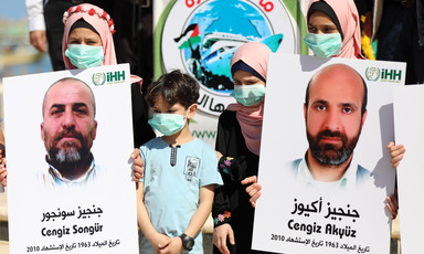 Children wearing face masks hold posters