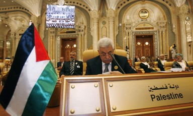 Mahmoud Abbas sits in a gold-themed room behind a sign with Palestine written on it