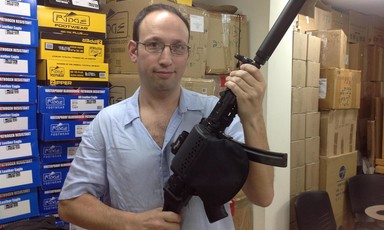 A man in glasses poses with a rifle