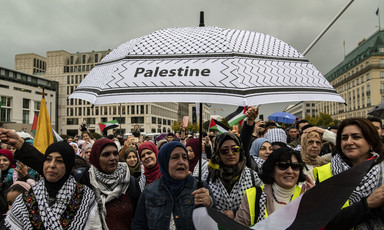 A group of women stand beneath a black-and-white umbrella emblazoned with the word 'Palestine'.