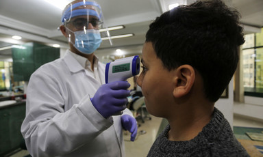 A doctor wearing a face mask is taking a boy's temperature