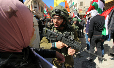 Israeli soldier holding rifle shouts at woman amid crowd