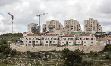 Landscape view of Israeli settlement and construction cranes