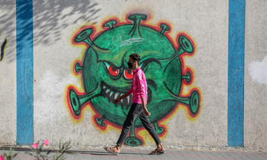 Man walks by a mural of a large virus particle