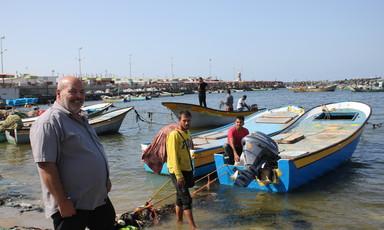 Three men stand near fishing vessels