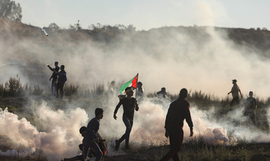 Protesters, one of them carrying a Palestine flag, are silhouetted against clouds of smoke