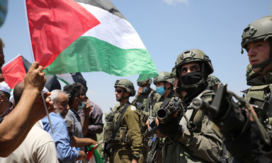 A Palestine flag waves in front of Israeli soldiers