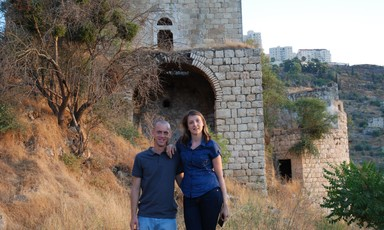 Couple stand in front of abandoned stone building on slope