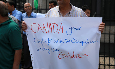 Man holds sign reading Canada your complicity with the occupation is killing our children