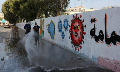 Men use hoses to spray sidewalk along wall with mural depicting a face in a coronavirus sphere and surgical masks