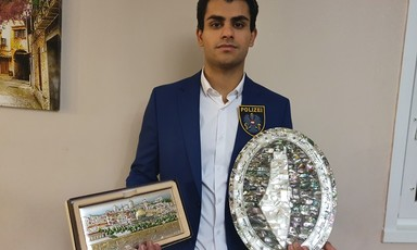 Man holds plaque in each hand