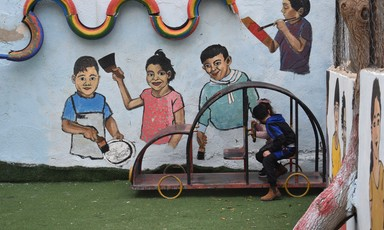 Children play outside in front of a brightly painted wall