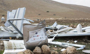 A demolished shelter beside a hill