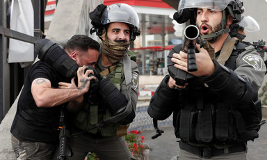An Israeli police officer puts a Palestinian in a choke hold while another officer points a gun