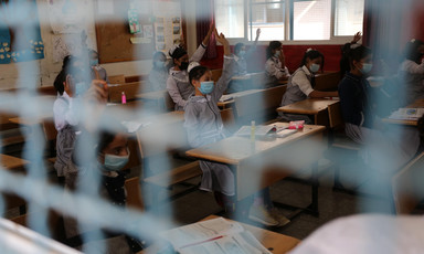 Schoolchildren are seen in their classroom through a wire mesh