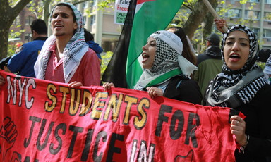 Demonstrators hold a banner that says Students for Justice in Palestine