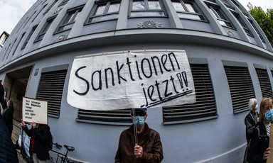 A man in face mask holds up a sign in German