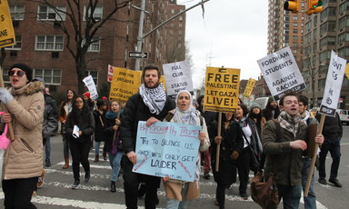 Demonstrators hold signs protesting Fordham's ban of SJP