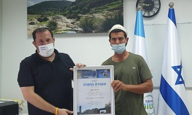 Two men wearing face masks hold framed certificate