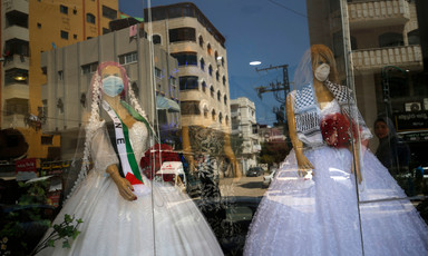 Two mannequins in wedding dresses and face masks are seen through through a shop window