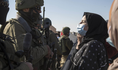 Palestinian woman wearing surgical mask faces an armed Israeli soldier