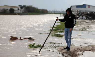 Man stands beside flooded land