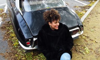 Woman smiles while sitting beside a car