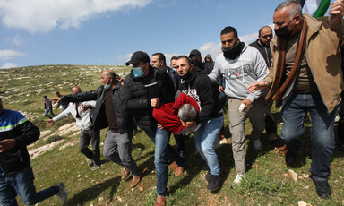 Men carry the body of an injured protestor