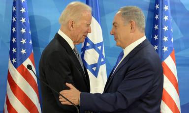 Joe Biden and Benjamin Netanyahu embrace in front of US and Israeli flags