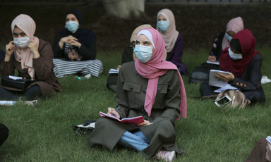 Women wearing masks sit outdoors