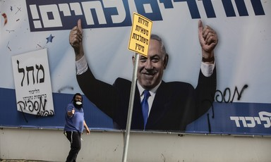An election poster covered with graffiti carries Benjamin Netanyahu's triumphant image