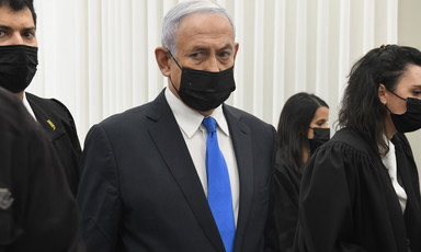 Netanyahu is seen from the waist up while wearing a mask inside a courtroom