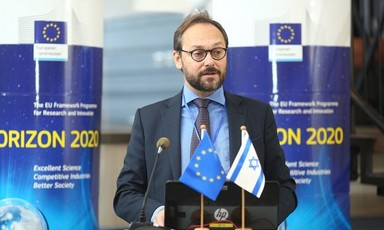 Emanuele Giaufret stands at podium with EU and Israel flags