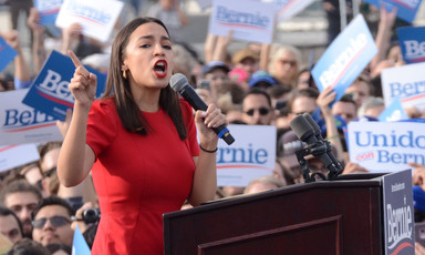 Woman speaks at podium in front of large crowd carrying signs