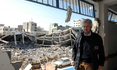 A man in a jacket stands with a ruined building in the background