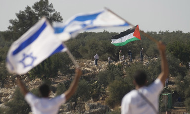 Two people wave Israeli flags opposite of a group with a Palestine flag in an olive orchard