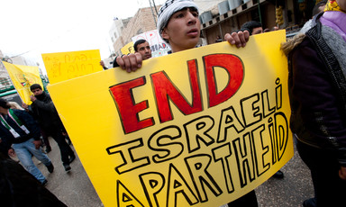 Youth carries sign reading End Israeli Apartheid while marching down street