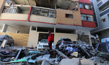 Man stands beside a badly damaged building