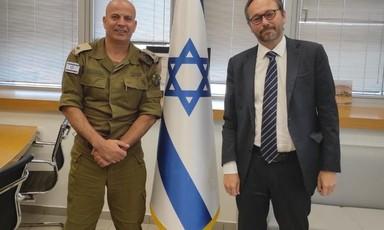 Man wearing military uniform stands beside man wearing suit