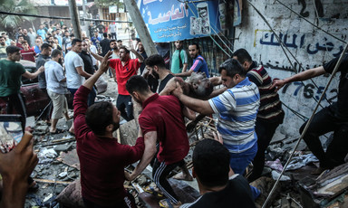 Men carry body of Yousif Abu Hussein as crowd on debris-strewn street looks on