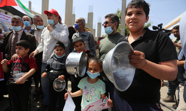 A group of people, some holding kitchen utensils