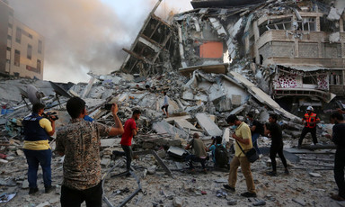 People stand by a pile of grey rubble from destroyed building