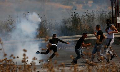 Men run away from cloud of tear gas smoke